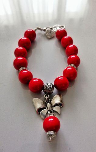 Bracelet en perles rouge. Fermoir mousqueton argenté. Breloque joli nœud argenté et une perle rouge.